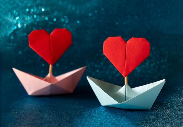 Rosa und blaues papierboot auf glitzerndem blauem hintergrund. romantisches valentinstagskonzept mit platz für text. Premium Fotos