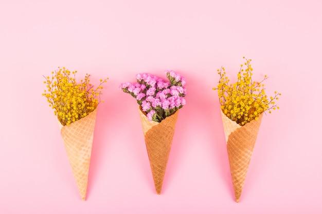 Rosa und gelbe blumen in den waffelkegeln für eiscreme auf einem hellen hintergrund. draufsicht flach liegend Premium Fotos