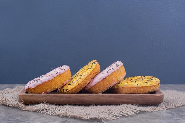 Rosa und gelbe cremefarbene donuts auf einer holzplatte Kostenlose Fotos