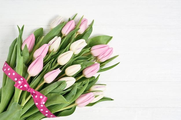 Rosa und weißer tulpenblumenstrauß verziert mit band Premium Fotos