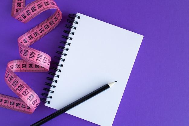 Rosa zentimeter und offener notizblock auf der violetten oberfläche. draufsicht. trockenes minimalkonzept. kopierraum. Premium Fotos