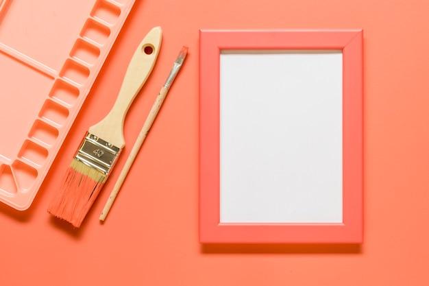 Rosa zusammensetzung mit leerem rahmen und ziehwerkzeugen auf farbiger oberfläche Kostenlose Fotos