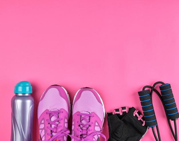 Rosafarbene damenschuhe, eine flasche wasser, handschuhe und ein springseil für den sport Premium Fotos