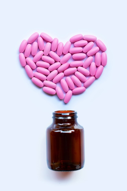 Rosafarbene medizinpillen auf weiß Premium Fotos
