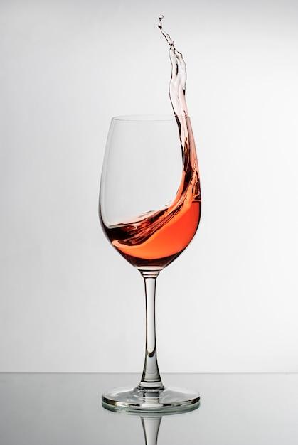 Rosafarbener wein, der oben die seite eines weinglases spritzt Premium Fotos