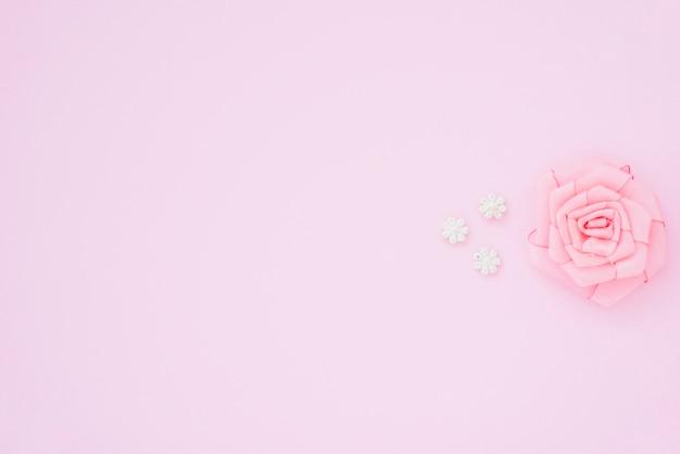 Rosarose gemacht mit band auf rosa hintergrund mit raum für das schreiben des textes Kostenlose Fotos