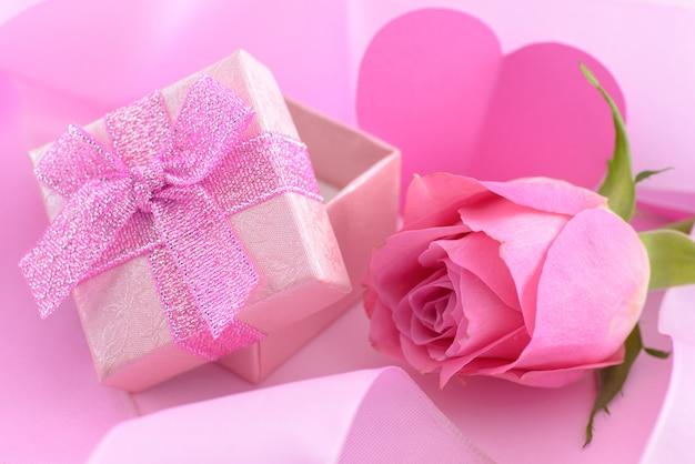 Rosarose und eine geschenkbox mit herzen, valentinstaghintergrund Premium Fotos