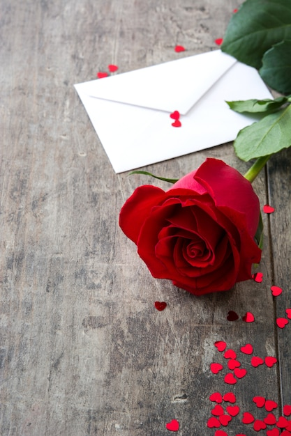 Rose mit umschlag und herzen auf hölzernem hintergrund Premium Fotos