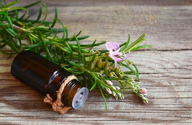 Rosemary-ätherisches öl in einer glastropfflasche mit frischem grünem rosmarinkraut auf altem holz Premium Fotos