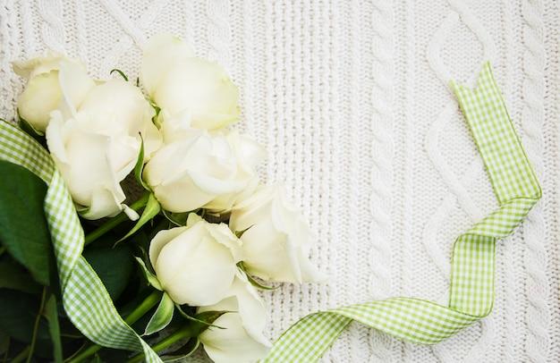 Rosen auf einem gestrickten weißen hintergrund Premium Fotos