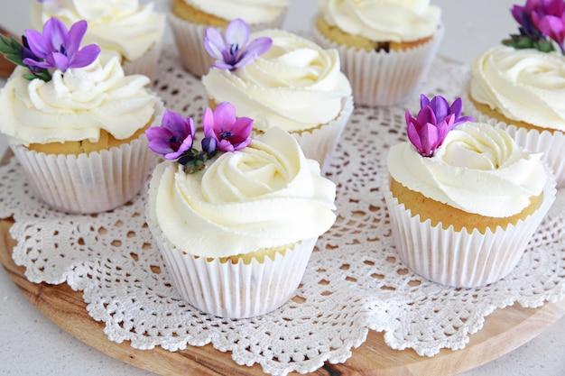 Rosen-blume, die vanillekleine kuchen mit purpurroten essbaren blumen bereift Premium Fotos