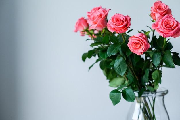 Rosen in einer transparenten vase auf einem grauen hintergrund mit platz für ihren text. Premium Fotos