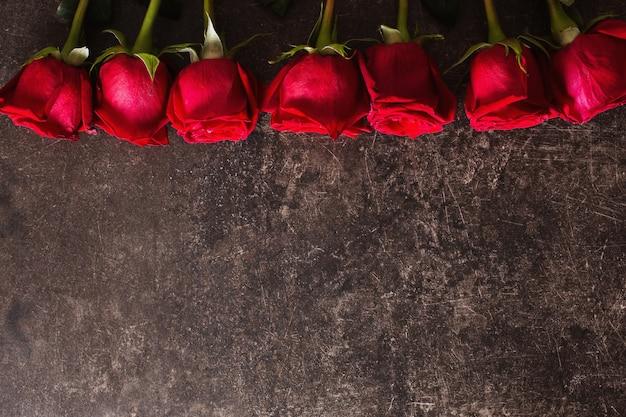 Rosen liegen auf einem dunklen marmortisch. großer schöner strauß roter rosen. texturfarben. ein geschenk für eine hochzeit, geburtstag, valentinstag. platz für text und design. flache lage, copyspace. Premium Fotos