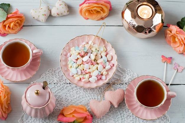 Rosen, tee in rosa tassen, herzen, süßigkeiten, dekor, zuckerdose, kerzenständer aus roségold Premium Fotos