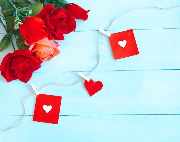Rosen über blauem hintergrund und herzen gefangen durch schnur. valentinstag hintergrund Premium Fotos