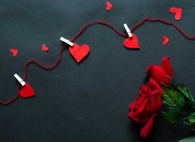 Rosen über schwarzem hintergrund und herzen gefangen durch schnur. prominente hintergrund. flache lage Premium Fotos