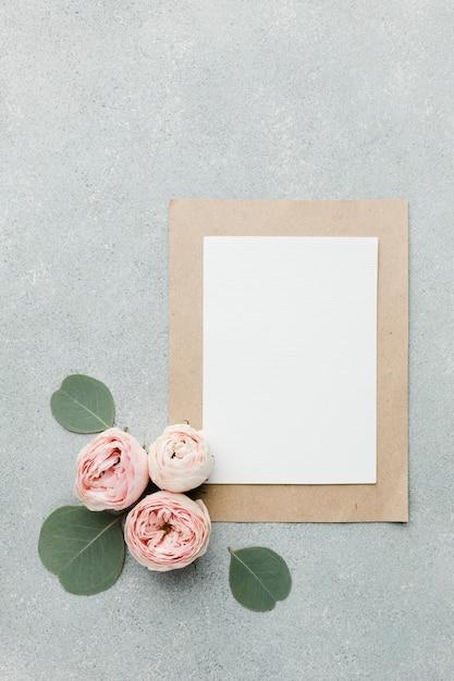 Rosen und blätter lagen flach mit leeren papieren und rahmen Kostenlose Fotos