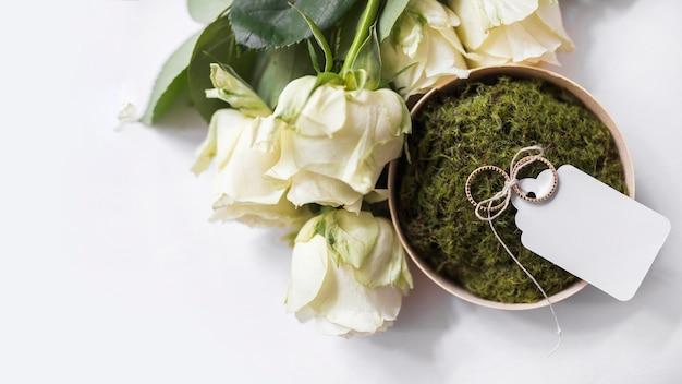 Rosen und eheringe mit weißem tag auf moos in der schüssel Kostenlose Fotos