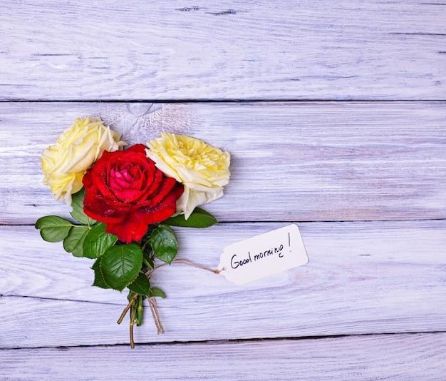 Rosen und eine papiermarke mit einer aufschrift guten morgen Premium Fotos