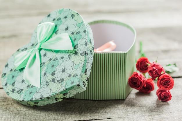Rosen und herzen auf hölzernem brett, valentinstaghintergrund Premium Fotos