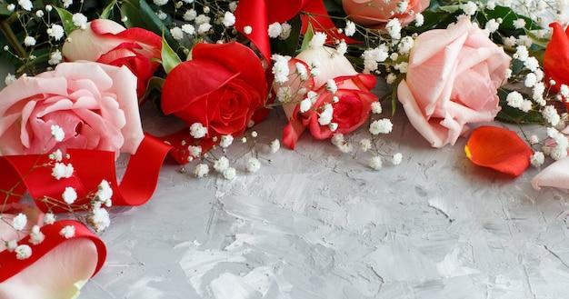 Rosen und kleine weiße blumen schließen auf einem grauen hintergrund Premium Fotos