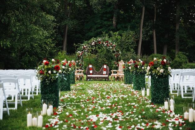 Rosenblumenblätter bedecken den grünen garten, der zu den traditionellen hindischen weddi bereit ist Kostenlose Fotos