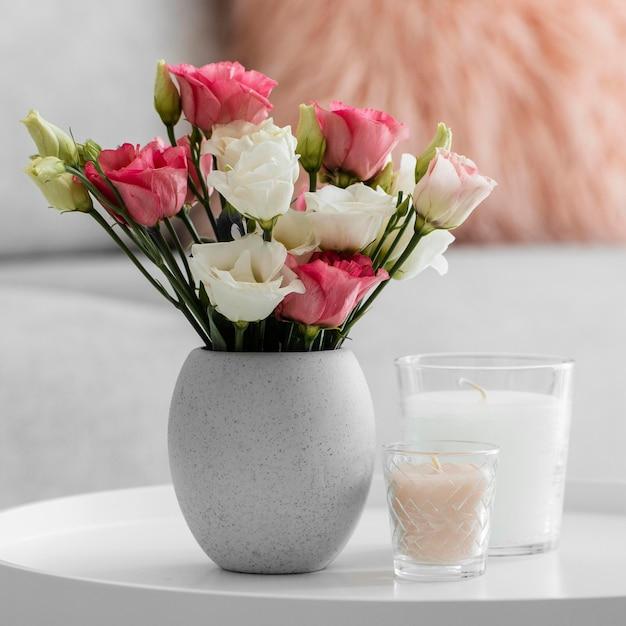Rosenstrauß in einer vase neben kerzen Kostenlose Fotos