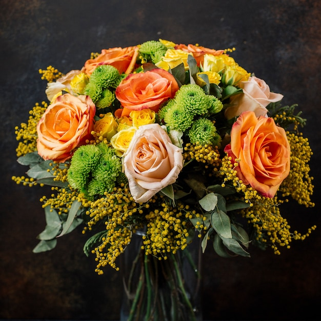 Rosenstrauß mit orange, gelben rosen, mimose im dunklen hintergrund Kostenlose Fotos