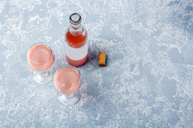 Roséwein-verkostungslayout. geöffnete flasche und zwei gläser mit roséwein auf grauem hintergrund. Premium Fotos