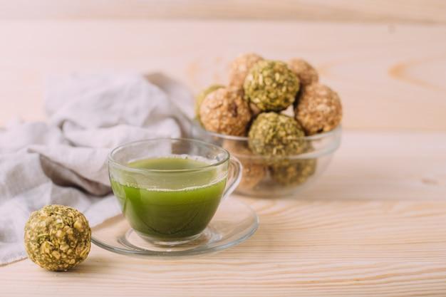 Rosinen mandelhonig glückskugeln. gesunde haferflocken-snacks energy balls mit hafer-mandel-butter und honig. tasse matcha-tee Premium Fotos