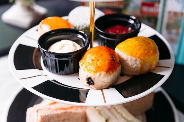 Rosinen-scone und einfacher scone auf schwarzweiss-farbplatte. mit marmelade und butter serviert. Premium Fotos