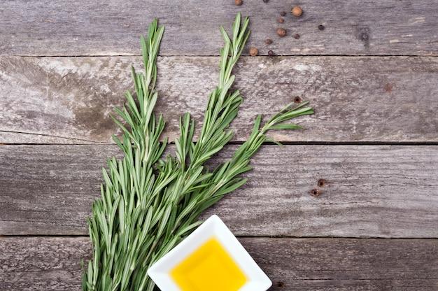 Rosmarin, olivenöl und pfeffer auf altem hölzernen hintergrund Premium Fotos