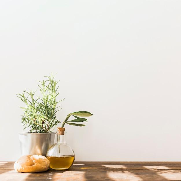 Rosmarinentopf mit frischer olivenölflasche und -brötchen auf holztisch Kostenlose Fotos
