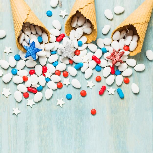 Rot; blaue und silberne sternstützen und bunte süßigkeiten wurden aus waffelkegel auf blauem strukturiertem hintergrund heraus verschüttet Kostenlose Fotos