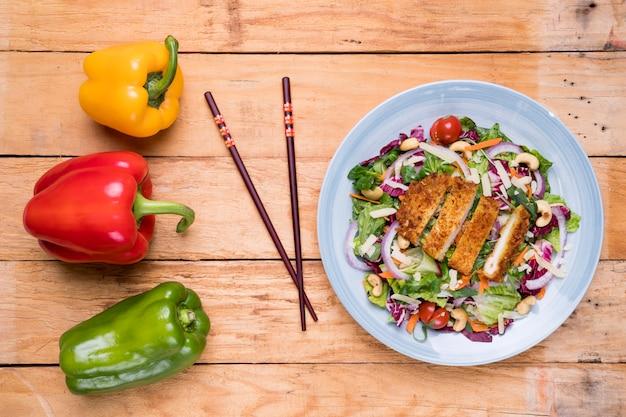 Rot; gelbe und grüne paprikaschoten mit essstäbchen und thailändischem salat auf dem schreibtisch Kostenlose Fotos