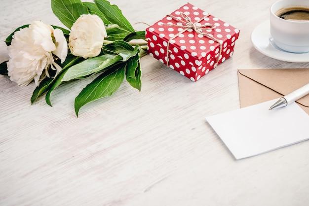 Rot punktierte geschenkbox, kraftpapier-umschlag und leere grußkarte, kaffeetasse und pfingstrose blüht blumenstrauß über weißem holz, copyspace. Premium Fotos