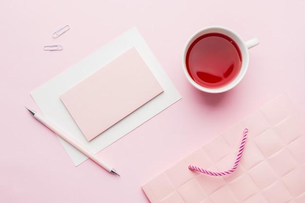 Rot-rosa gegenstände tasse tee und notizblock für text auf rosa pastellhintergrund. Premium Fotos
