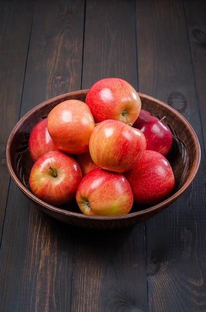 Rote äpfel auf einem dunklen rustikalen hintergrund in einer lehmschüssel. flach liegen. Premium Fotos