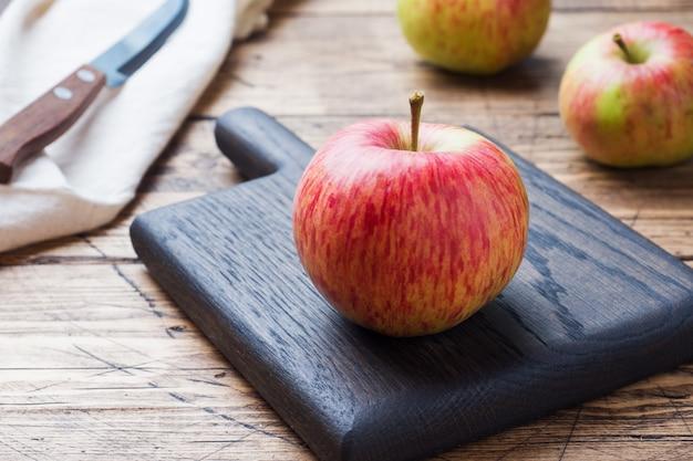 Rote äpfel auf einem holztisch Premium Fotos