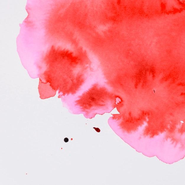 Rote aquarellfarbe, die auf weißen hintergrund fließt Kostenlose Fotos