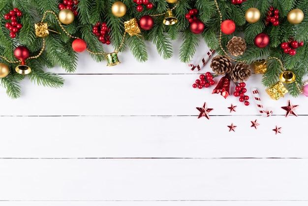 Rote bälle der weihnachtsgeschenkbox mit fichtenzweigen, kiefernkegel, rote beeren auf hölzernem backg Premium Fotos