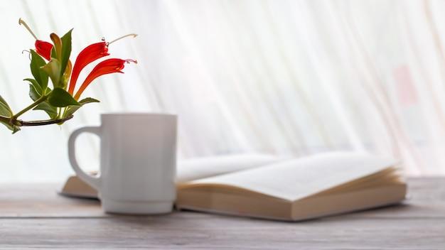 Rote blumen der zimmerpflanze nahe offenem buch und tasse kaffee Premium Fotos