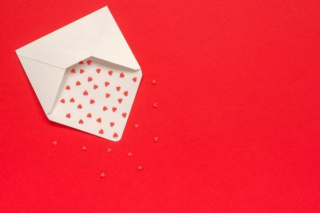 Rote bonbons besprüht süßigkeitsherzen fliegen aus weißbuchumschlag auf rotem hintergrund heraus Premium Fotos