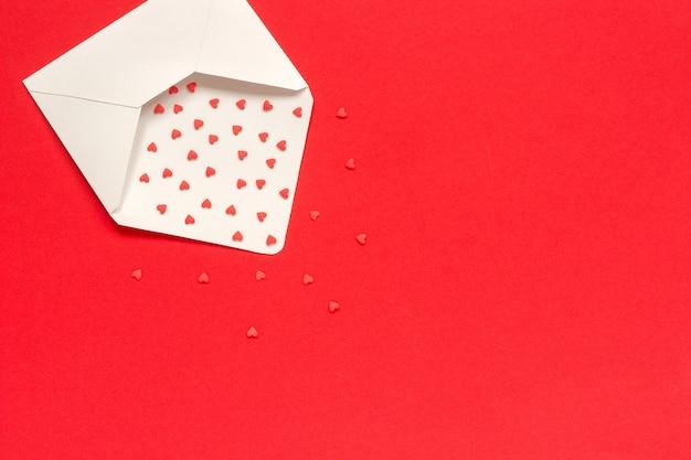 Rote bonbons besprüht süßigkeitsherzen fliegen aus weißbuchumschlag auf rotem hintergrund heraus. Premium Fotos