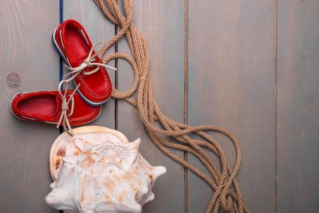 Rote bootsschuhe nahe großem oberteil und seil auf hölzernem. Premium Fotos