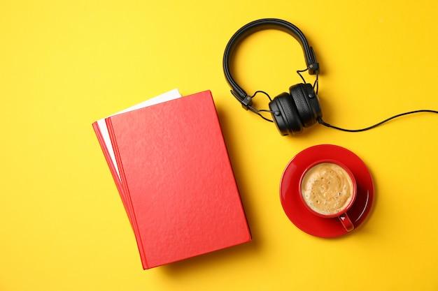 Rote bücher, kopfhörer und tasse kaffee auf gelbem hintergrund, draufsicht Premium Fotos