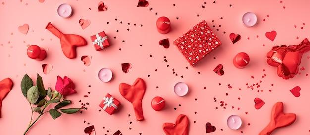 Rote dekorationsballons, kerzen, konfetti und geschenke draufsicht flach lagen auf rosa hintergrund Premium Fotos