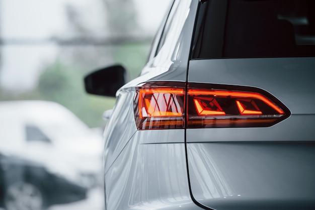Rote farbe beleuchtung. partikelansicht des modernen weißen luxusautos, das tagsüber drinnen geparkt wird Kostenlose Fotos