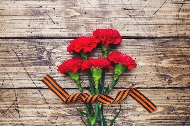 Rote gartennelken und st- georgefarbband auf hölzernem hintergrund. Premium Fotos