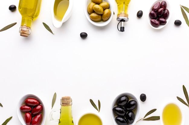 Rote gelbe schwarze oliven der draufsicht in den löffeln mit ölflaschen und kopienraum Kostenlose Fotos